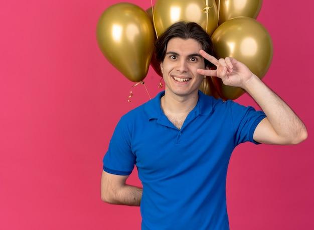 Glücklicher gutaussehender kaukasischer mann steht vor heliumballons und gestikuliert siegeshandzeichen