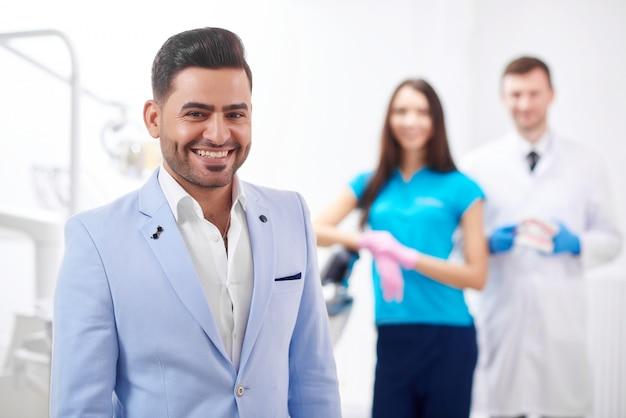 Glücklicher gutaussehender männlicher geschäftsmann lächelnd, der an der zahnarztpraxis sein arzt und krankenschwester steht, die copyspace gesundheitsmedizinzahnmedizin-dienstkonzept aufstellen.