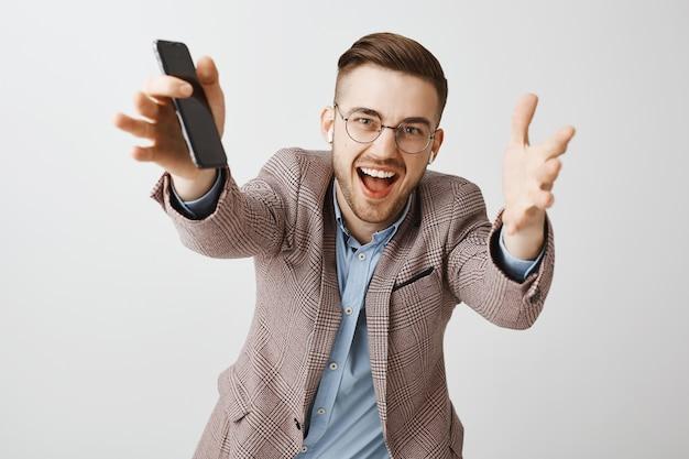 Glücklicher gutaussehender männlicher unternehmer, der hände nach vorne erreicht und musik mit drahtlosen kopfhörern und wiedergabeliste in der handy-app hört