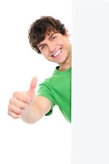 Glücklicher gutaussehender mann, der daumen hoch zeigt, schauen vom weißen leeren banner heraus