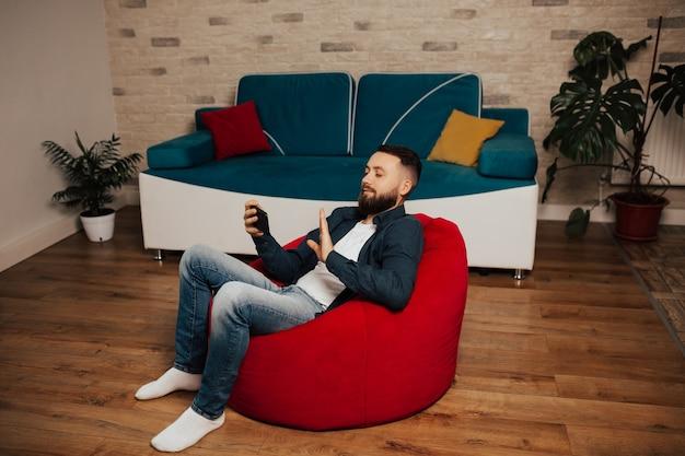 Glücklicher gutaussehender mann, der einen videoanruf spricht. ein mann kommuniziert mit freunden per videoanruf über ein smartphone.