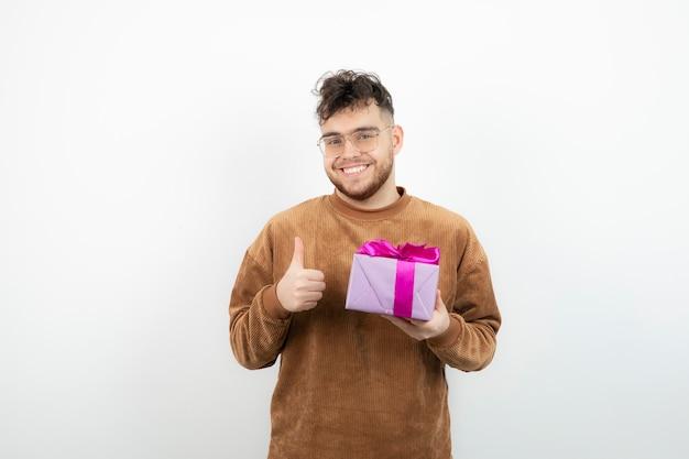 Glücklicher gutaussehender mann, der sein feiertagsgeschenk hält und daumen aufgibt.