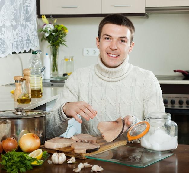Glücklicher gutaussehender mann, der steak des heringshailles kocht