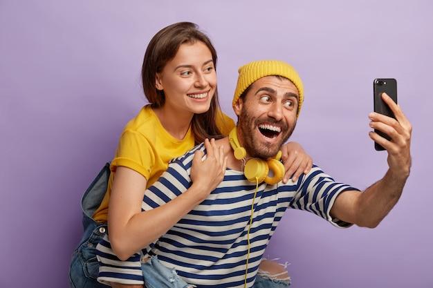 Glücklicher gutaussehender mann gibt huckepackfahrt zur freundin, macht selfie auf dem handy und hat spaß, trägt freizeitkleidung