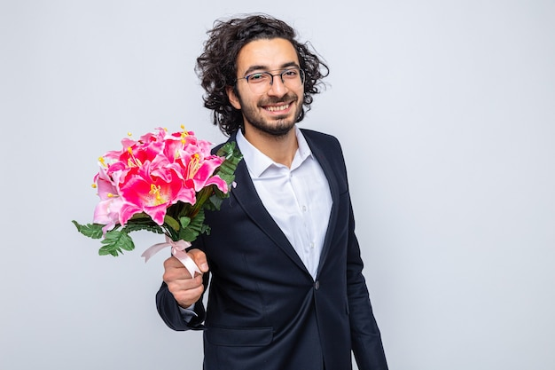 Glücklicher gutaussehender mann im anzug mit blumenstrauß, der fröhlich lächelt