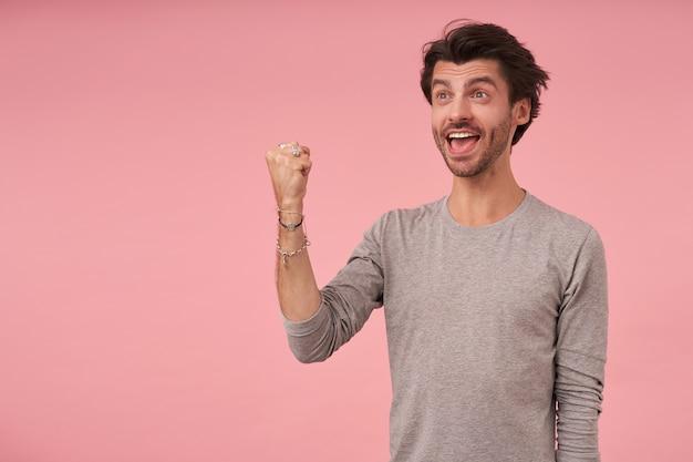 Glücklicher gutaussehender mann mit trendigem haarschnitt, der grauen pullover trägt, steht, beiseite schaut und faust in ja-geste hebt, glücklich ist und weit lächelt