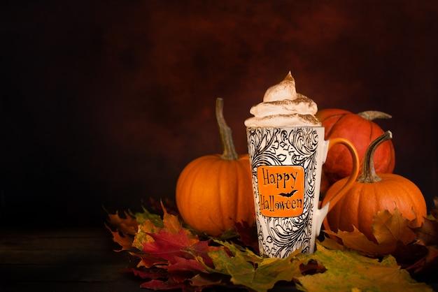 Glücklicher halloween-becher mit geflüsterter sahne vor orange kürbissen auf dunkelheit