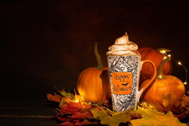 Glücklicher halloween-becher mit geflüsterter sahne vor orange kürbissen auf dunklem hintergrund.