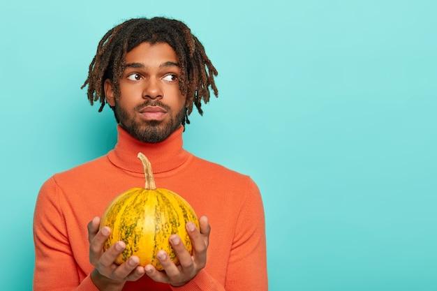 Glücklicher halloween-tag. der nachdenkliche bärtige mann hält einen kleinen kürbis in der hand und denkt darüber nach, tolle herbstferien zu organisieren, gekleidet in einen orangefarbenen rollkragenpullover