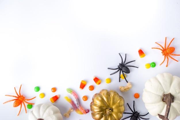 Glücklicher halloween-tagesfeiertagshintergrund. flache lage mit süßigkeiten und dekorationen für kinderpartys, eimerpackung mit spinnen, süßigkeiten, fledermaus, auf weißem tischkopierraum-draufsichtsrahmen