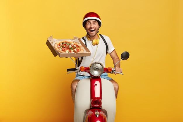 Glücklicher hart arbeitender hübscher männlicher fahrer auf roller mit rotem helm, der pizza liefert