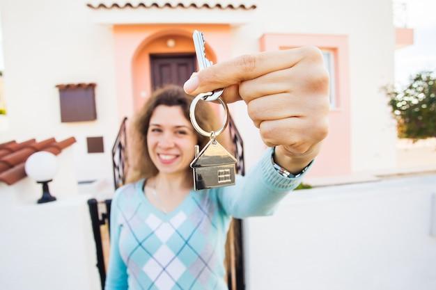 Glücklicher hausbesitzer oder mieter, der schlüssel zeigt und sie ansieht.