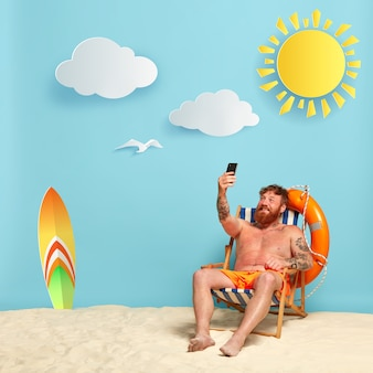 Glücklicher hemdloser bärtiger rothaariger mann, der am strand aufwirft