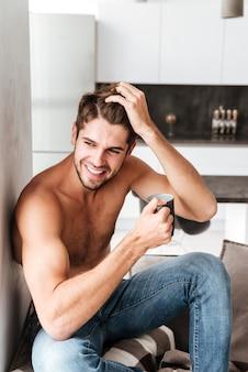 Glücklicher hemdloser junger mann, der kaffee auf der küche sitzt und trinkt