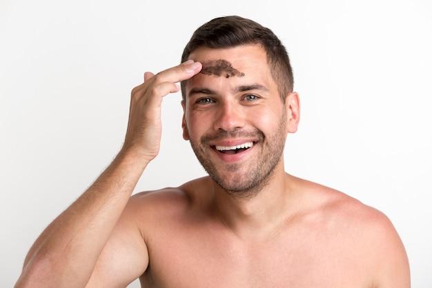 Glücklicher hemdloser junger mann, der schwarze maske auf gesicht gegen weißen hintergrund anwendet