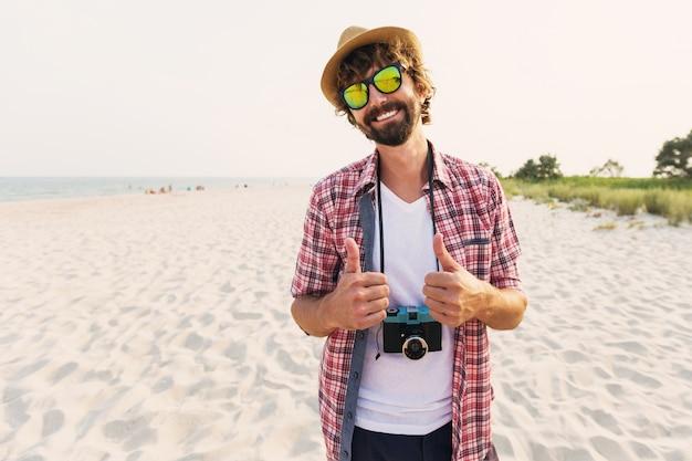Glücklicher hipster-mann mit bart und retro-fotokamera