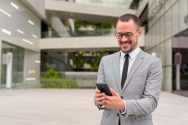 Glücklicher hispanischer kahler bärtiger geschäftsmann, der telefon mit brille in der stadt im freien verwendet