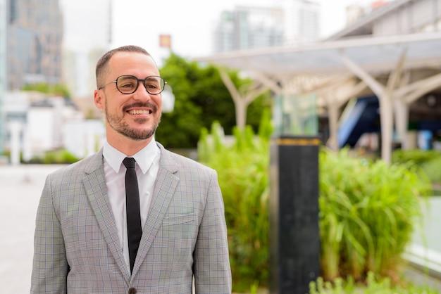 Glücklicher hispanischer kahler bärtiger geschäftsmann mit brillen, die in der stadt draußen denken