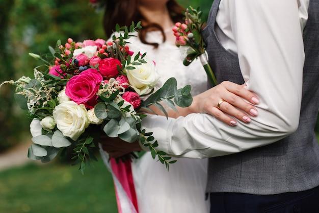 Glücklicher hochzeitstag draußen. leidenschaftliche umarmungen eines liebenden paares. nahaufnahme bräutigam mit knopfloch sanft umarmt die braut mit roten blumenstrauß. hochzeit romantischen moment. frisch verheiratet