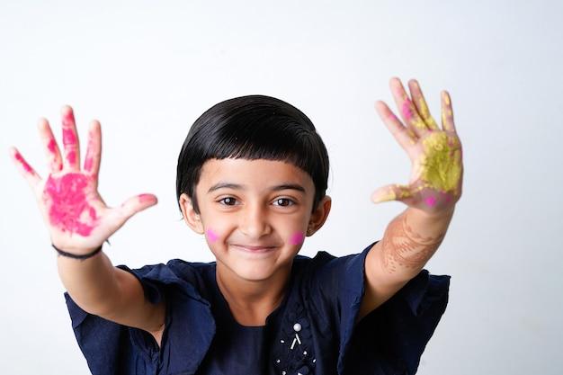Glücklicher holi-gruß - nettes kleines indisches mädchen mit bunten händen, lokalisiert über weißem hintergrund