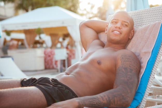 Glücklicher hübscher afrikanischer mann, der genießt, in der sonne am pool des hotels zu liegen, kopieren raum. fröhlicher junger athletischer mann, der sich sonnt und seine sommerferien genießt