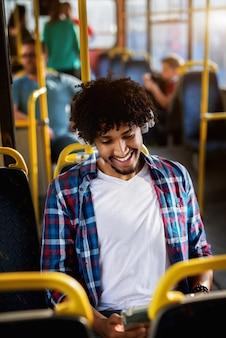 Glücklicher hübscher afroamerikanischer mann, der in einem bus sitzt und die musik hört.