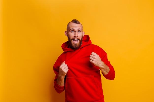 Glücklicher hübscher brutaler bärtiger mann, der warmen roten wintertrend-fleece-kapuzenpulli trägt