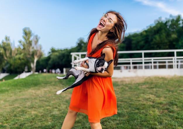 Glücklicher hübscher frauenpark, der boston-terrier-hund hält, positive stimmung lächelnd, trendiger sommerstil, orange kleid, sonnenbrille tragend, mit haustier spielend, spaß, bunt
