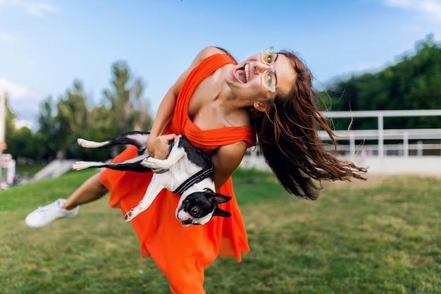 Glücklicher hübscher frauenpark, der boston-terrier-hund hält, positive stimmung lächelnd, trendiger sommerstil, orange kleid, sonnenbrille tragend, mit haustier spielend, spaß habend, bunt, langes haar winkend