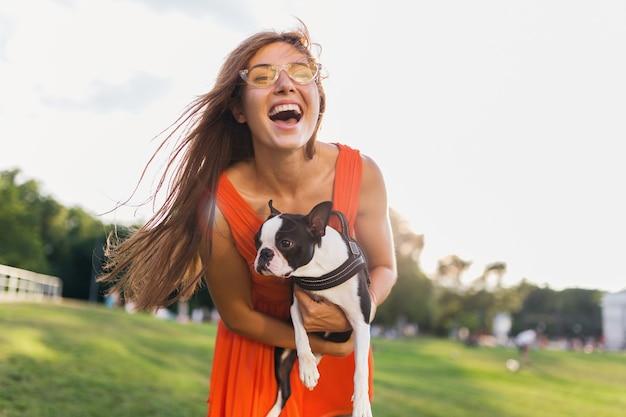 Glücklicher hübscher frauenpark, der boston terrier-hund hält, positive stimmung lächelnd, trendiger sommerstil, orange kleid, sonnenbrille tragend, spielt mit haustier, spaß, sonnige wochenendunterhaltung hat