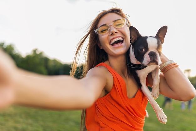 Glücklicher hübscher frauenpark, der selfie-foto macht, boston-terrier-hund hält, positive stimmung lächelt, trendige sommerart, orange kleid trägt, sonnenbrille, mit haustier spielt, spaß hat