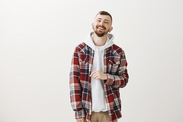 Glücklicher hübscher hipster-typ, der lacht und lächelt