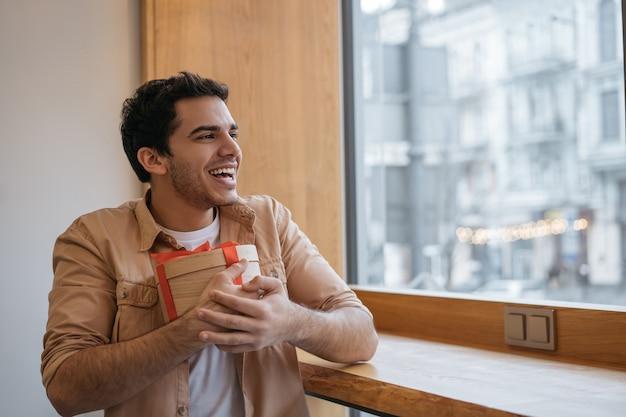 Glücklicher hübscher indischer mann, der geschenkbox hält, im modernen café sitzt und durch das fenster schaut