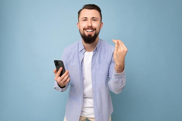 Glücklicher hübscher junger brünetter unrasierter mann mit bart, der stilvolles weißes t-shirt und blaues hemd trägt