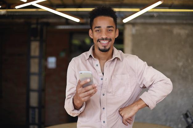 Glücklicher hübscher junger dunkelhäutiger mann mit bart, der über modernem büroinnenraum in der freizeitkleidung aufwirft, fröhlich schaut und seine perfekten weißen zähne demonstriert
