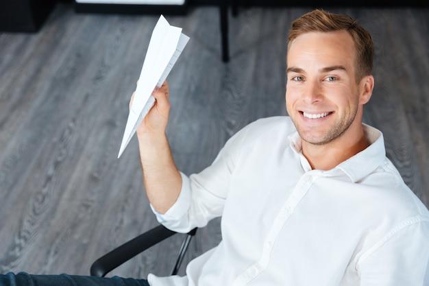 Glücklicher hübscher junger geschäftsmann, der im büro sitzt und papierflieger wirft