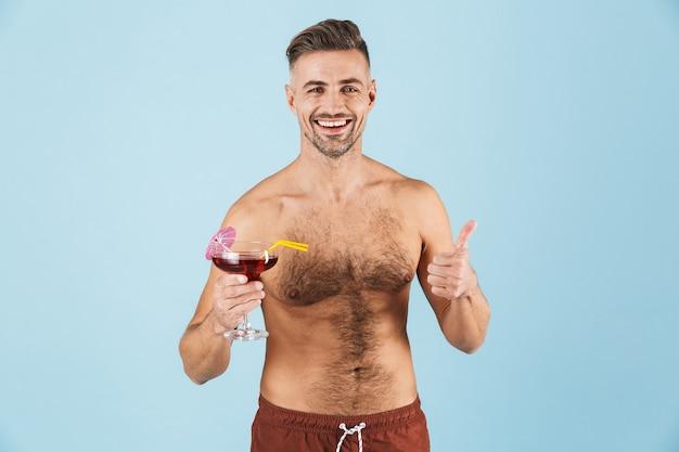 Glücklicher hübscher junger hemdloser mann, der strandshorts trägt, die über blau stehen, cocktail trinken