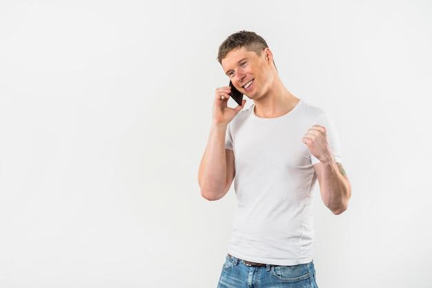 Glücklicher hübscher junger mann, der ihre faust spricht auf mobiltelefon gegen weißen hintergrund zusammenpreßt