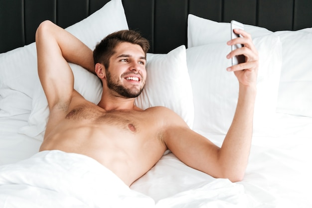 Glücklicher hübscher junger mann, der liegt und smartphone im bett benutzt