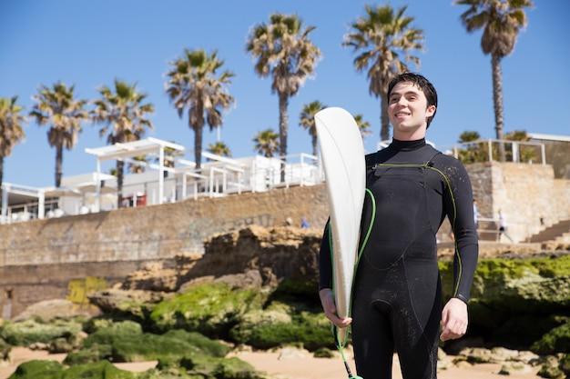 Glücklicher hübscher junger mann, der surfbrett auf sonnigem strand hält