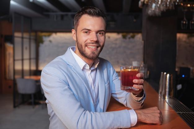 Glücklicher hübscher junger mann, der zur kamera lächelt und mit seinem cocktailglas jubelt