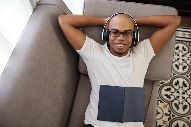 Glücklicher hübscher junger schwarzer mann im weißen t-shirt, der auf sofa entspannt, musik in kopfhörern hört und kamera betrachtet, ansicht von oben