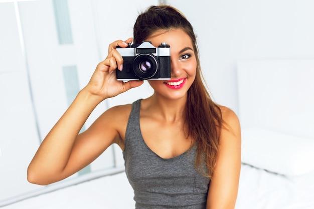 Glücklicher hübscher lächelnder fotograf, der bild mit retro-kamera macht
