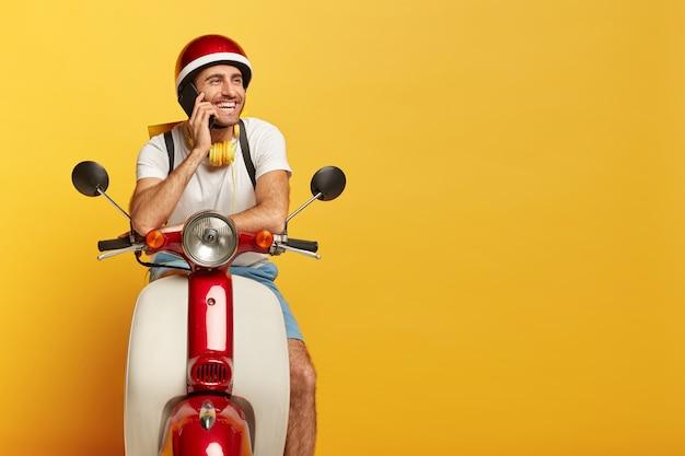 Glücklicher hübscher männlicher fahrer auf roller mit rotem helm
