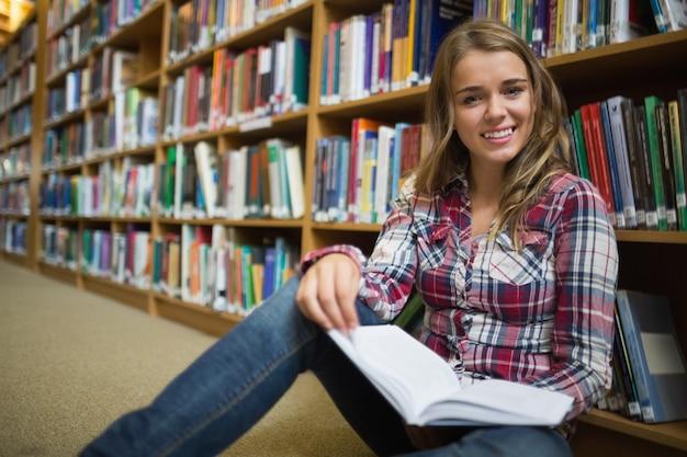 Glücklicher hübscher student, der auf bibliotheksboden-lesebuch sitzt