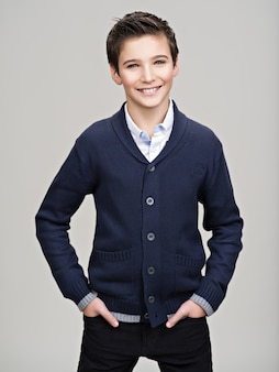 Glücklicher hübscher teenager, der im studio als model aufwirft.