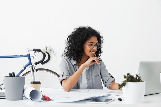 Glücklicher hübscher weiblicher ingenieur, der über büroinnenraum sitzt und dokumente hat