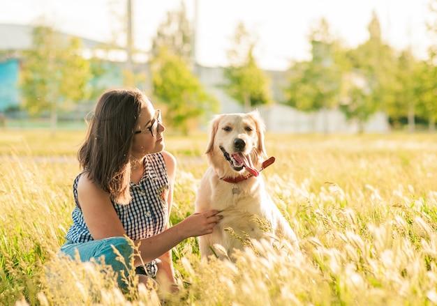 Glücklicher hund retriever und besitzer, der natur im park genießt
