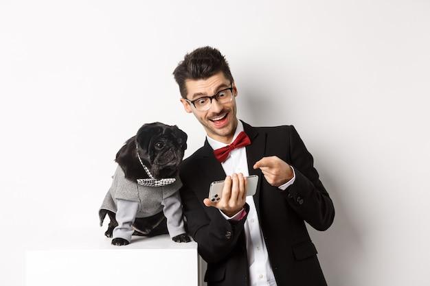 Glücklicher hundebesitzer, der etwas zeigt, um auf handy, mann und mops zu tragen, die ausgefallene kostüme tragen, die über weiß stehen.