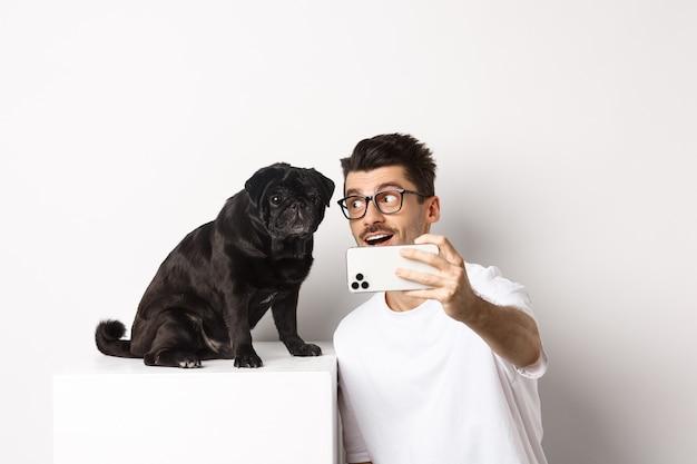Glücklicher hundebesitzer, der selfie mit niedlichem schwarzen mops nimmt, lächelt und mit liebe auf hündchen schaut, handy hält, weiß